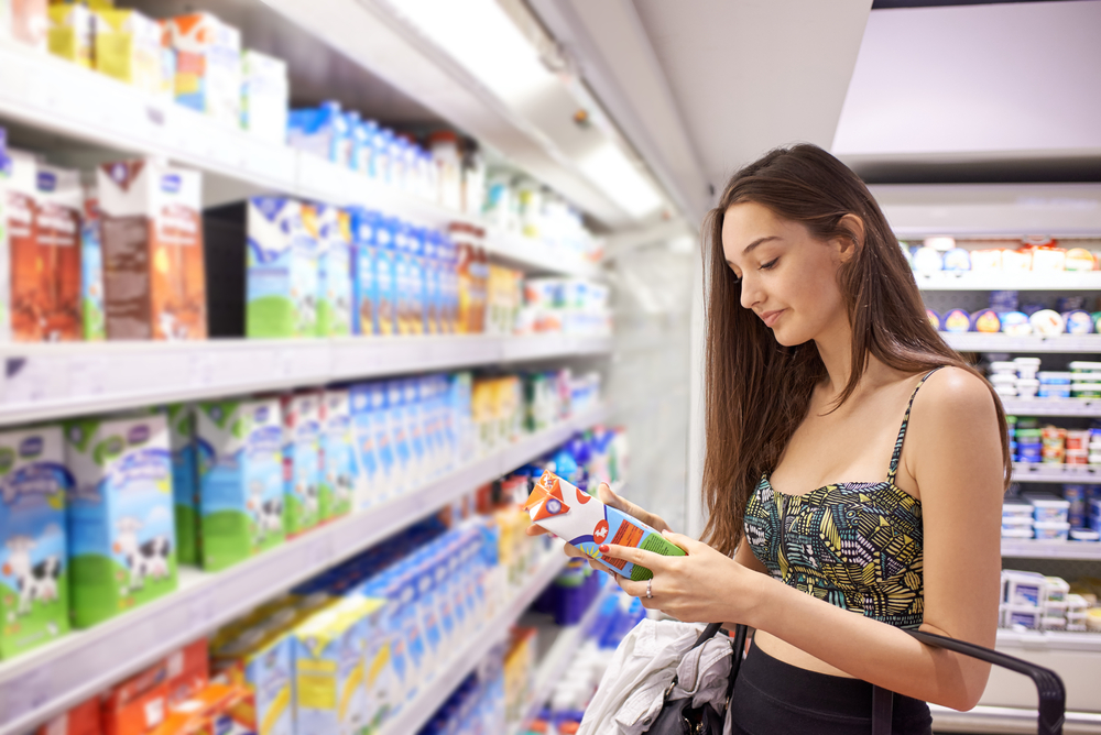 Woman reading food label under bright led grocery store lighting